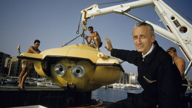 Underwater pioneer Jacques Cousteau guides his latest underwater research vessel for an expedition to study the Caribbean's teeming sea life. National Geographic sponsored the expedition. (Thomas J. Abercrombie/National Geographic)