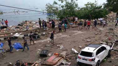People walk past dead bodies a day after a tsunami hit Palu, on Sulawesi island. Picture: AFP