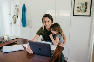 IMAGE ID: A parent and their child sit at a desk together with a laptop in front of them. End image ID. Source: ClimateClever