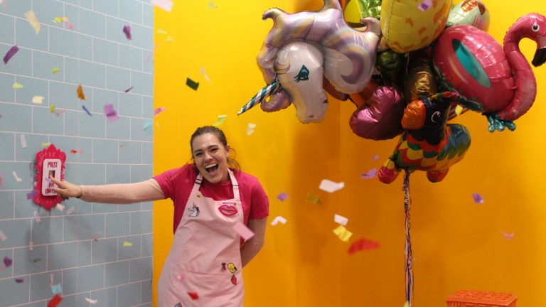 """A smiling staff member presses a button. It says """"press for confetti"""" and she is showered in it!"""