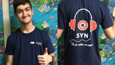 "Matt stands in front of a blue and green background wearing a navy blue shirt. The rear of the shirt features the SYN logo with the text ""On air, online, on campus"". The front of the shirt features the SYN and RMIT University logos."
