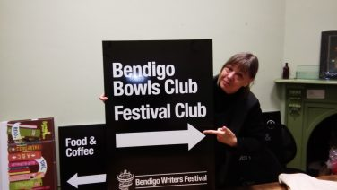 Rosemary Sorensen holds up sign promoting Bendigo Writers Festival