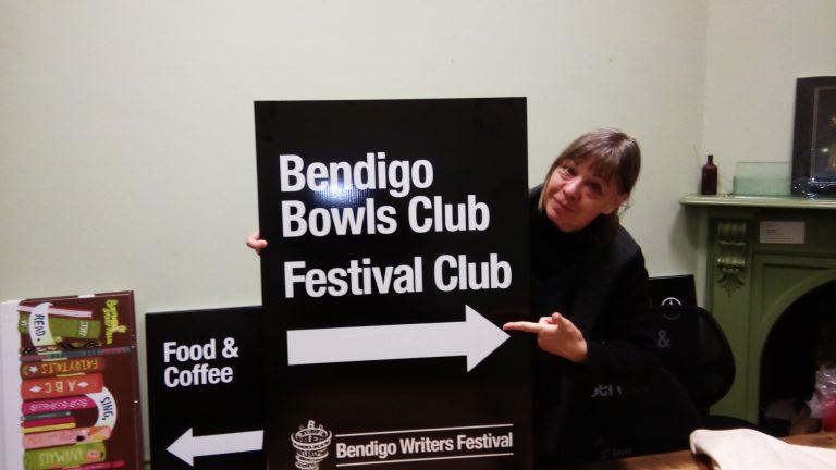 Rosemary Sorensen holds up sign promoting Bendigo Writers Festival