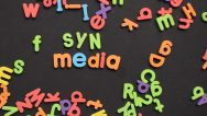 """Magnetic letters with the word """"SYN Media"""" in focus."""