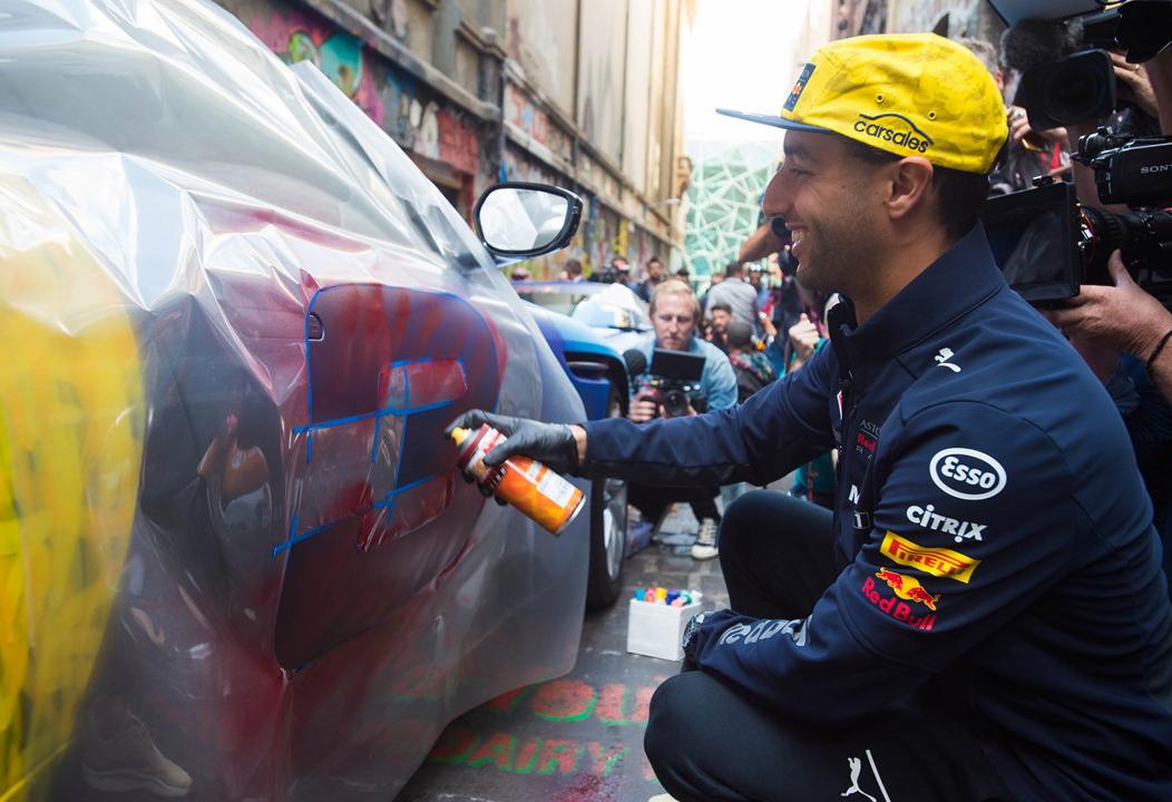 Daniel Ricciardo gets to work painting an Aston Martin in Hosier Lane.