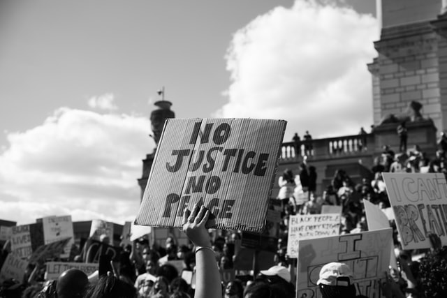 "A grayscale image of a Black Lives Matter protest, zoomed on a sign that reads ""No Justice No Peace"""