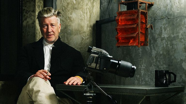 A photo of David Lynch used in promotional material for his latest film 'The Art Life'. It contains Mr. Lynch sitting down on a chair in a dark room with a Canon DSLR and black mug sitting on a table beside him.