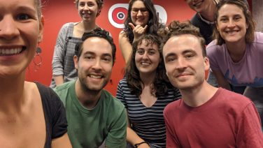 Image Caption: A photo of the SYN staff [from left to right] Molly, Cambpell (outgoing GM), Maddy, Erin, Evrim (incoming GM), Danny (incoming SYN Media Learning Coordinator), Johan and Merryn (outgoing SYN Media Learning Coordinator).