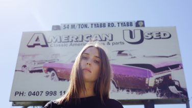 Ali Barter stands in front of a billboard