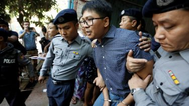 Detained Reuters journalist Wa Lone is escorted by police after a court hearing in Yangon, Myanmar April 11, 2018. REUTERS/Ann Wang